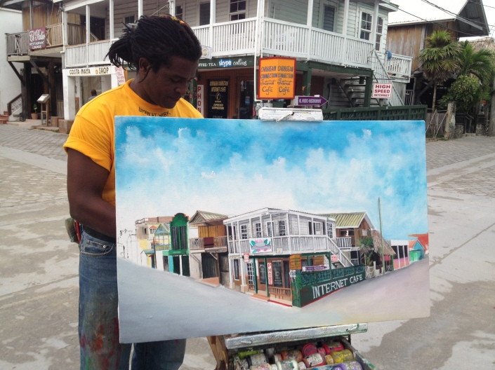 Terrell is a street painter working on Barrier Reef Drive this morning. He'd just finished this painting of the corner directly behind him on which sits the Caribbean Connection Internet Cafe.