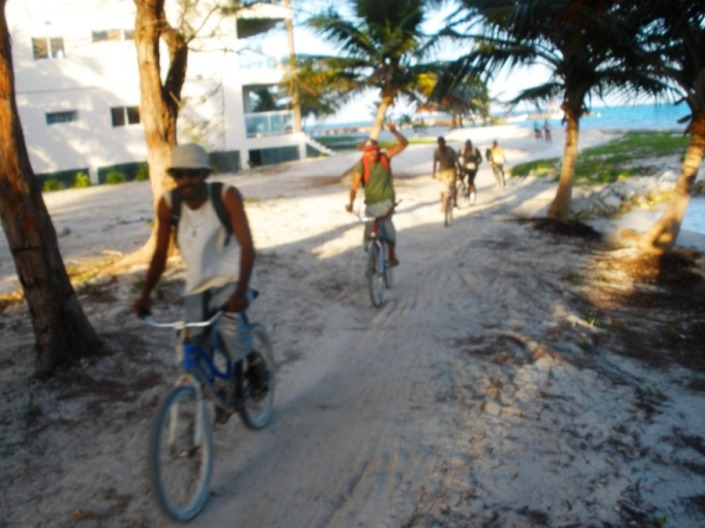 Locals returning home from work along the beach path on Ambergris Caye.