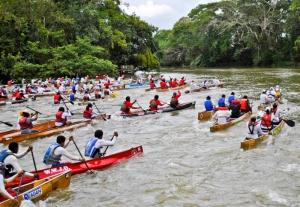 Canoes sprint down the river in the Belikin La Ruta Maya River Challenge.  (Photo courtesy of larutamayabelize.com.)