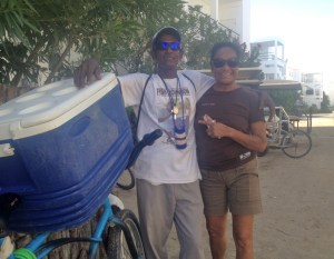 Feature section: Meet Fish Johnson. He pedals around San Pedro Town with this cooler filled with fresh fish and shrimp (conch and lobster in season). He stops by the complex we live in a couple of times a week. We picked up some grouper and shrimp from Fish Johnson the other day and Rose (on the right) made an incredible dish with rice, coconut milk, veggies, fish and shrimp last night. Fish says he has been at the fishmonger business for 35 years.  Has his own T-shirts for sale and hands out business cards to prospective customers. Call in and he will deliver stat, he promises.