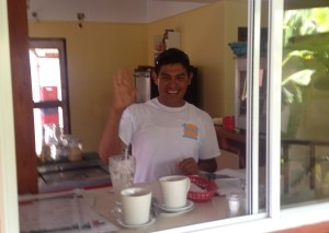 Our new pal Wilbert waves from behind the counter at Coconut Cafe in San Pedro Town.