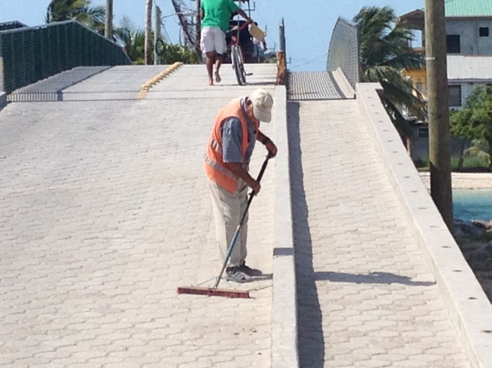 This is Fred. Every day he sweeps the only bridge in San Pedro Town. I think he does a heck of a job and every day that I cycle over the bridge and he is there I make a point to say hello and thank you.