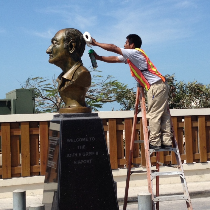 Manuel cleans and buffs the bust of John E. Greif II in front of the eponymously named airport in San Pedro Town, Belize. According to the plaque on the front Greif is the father of aviation and tourism in San Pedro.