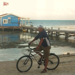 "That's me in my patented Heroic Man on Bicycle"" stance, which people have begun to notice all over Ambergris Caye. Actually, this photo has nothing to do with the post. Just a shot Rose took in front of Crazy Canuck's bar shortly after I walked right through the middle of an intense horseshoe tournament. I am really thinking: ""How many other ways can i embarrass myself?"""