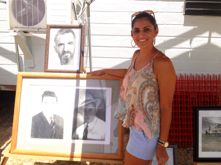 Wilema Alamilla stands proudly beside a photo of her grandfather, Octavio Alamilla, a founding member of the island's first fishermen's cooperative. The photo is part of historic exhibit at the San Pedro House of Culture across the street from the town footballl field on Back Street.