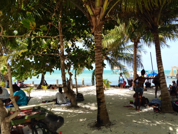 Caye Caulker LobsterFest fans sought cover in the shade of palm trees during the mid-day heat.