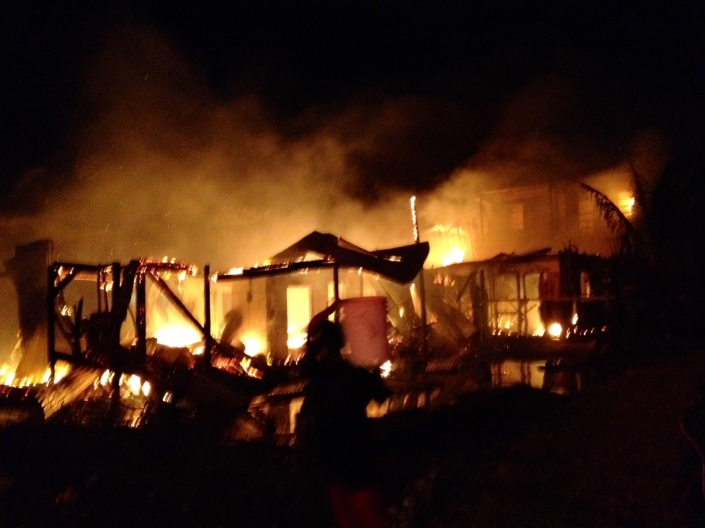 Fire in the San Juan area of San Pedro levels several homes and an apartment building along the canal tonight, July 7, 2014.