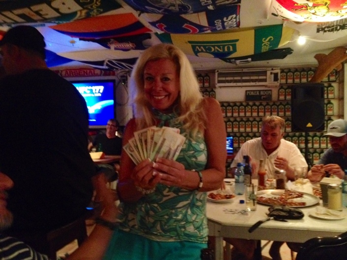 Ride, Sally, ride: Winner of the season's last poker run in San Pedro, Sally Backalukas flashes the cash and a wining smile at the finish, Pedro's Hotel.