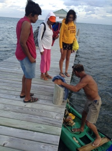 Jose pulls up in his kayak to sell conch, lobster, fish -- whatever he can gather in a day's work off the barrier reef. Rose and Caira and a neighbor scrutinize his catch. He came back today with a rockfish for me.