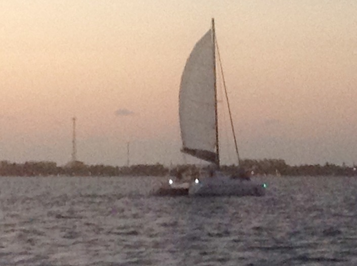 After sunset, racing other catamarans back north toward the rising moon, off San Pedro, Ambergris Caye, Belize.