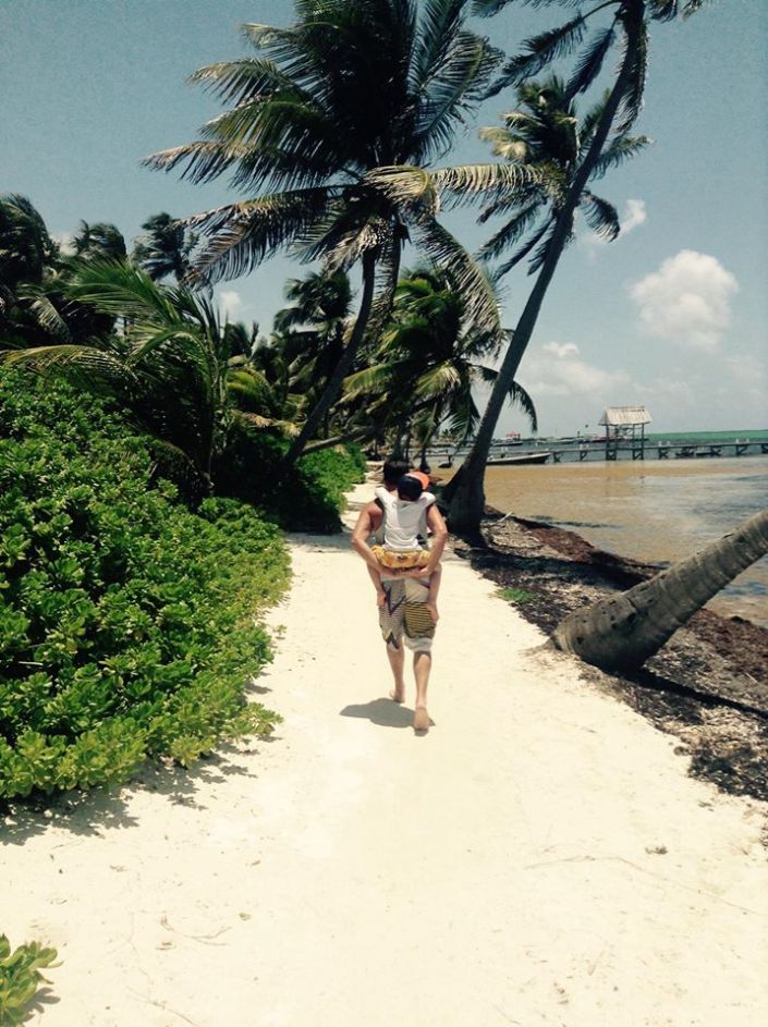 Brody hitches a ride on his dad's back on one hike up the Ambergris Caye coast.