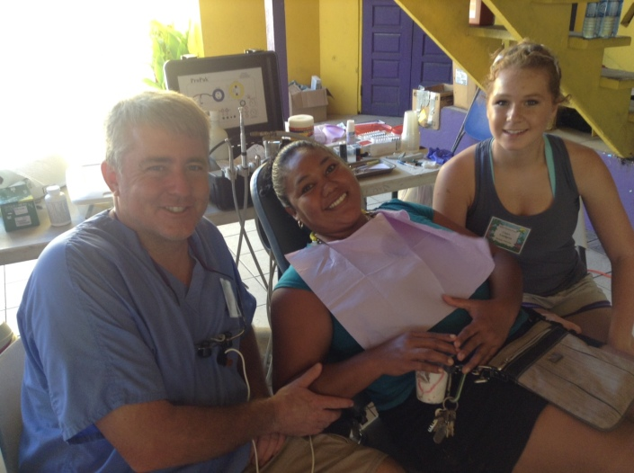 """Dr.David Landgren and his daughter Claire, 16, of Hastings, Nebraska, are on their first dental mission to Belize and both have seen it as the experience of a lifetime. Dr. Landgren spoke of the """"dichotomy"""" that exists on Ambergris Caye between the extreme poverty of San Mateo and the luxe life in resorts along the coast. Here they are working on Suyapa Leslie of San Pedro."""