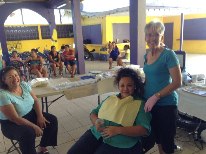Jan English of Princeton, Illinois has returned to San Predro for at least her third time, performing extractions and fillings on residents. In the chair is Adayli Moncada of Caye Caulker while her mother-in-law Rosie Wejbe waits nearby.