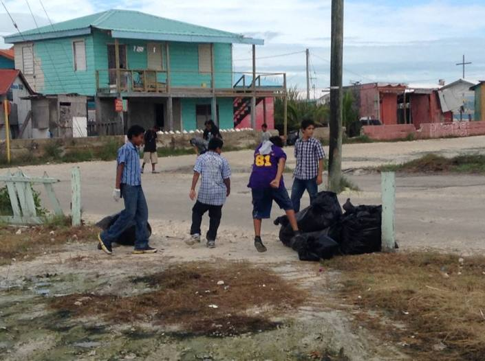 Holy Cross students tackle the trash near the entrance to the San Mateo neighborhood.