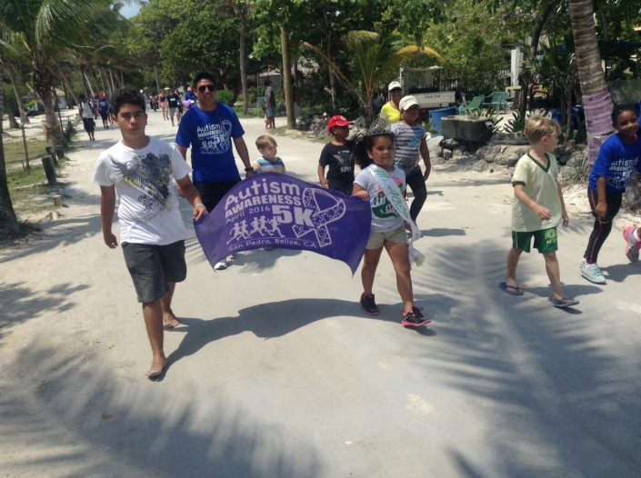 Little Ms ACES (Ambergris Caye Elementary School) and her entourage carry the banner for the race and their school on Boca del Rio.