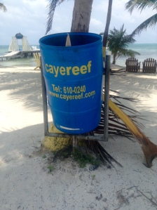 "Interesting solution to ""roaming"" trash barrels"" from Caye Caulker -- barrels are attached to galvanized steel pipe frames and holes are drilled into the bottoms of the cans for drainage."