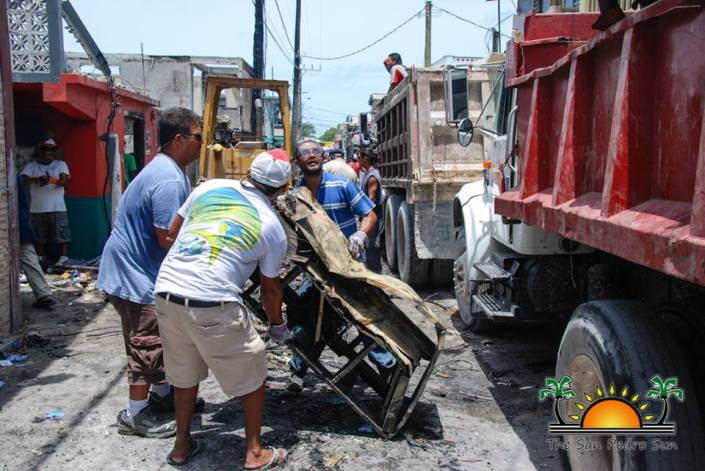One truck at a time, the job is getting done. Volunteers and workers join together today to clean up the aftermath of the fire at Buccaneer Street & Pescador Drive in Town. (Photo by San Pedro Sun)