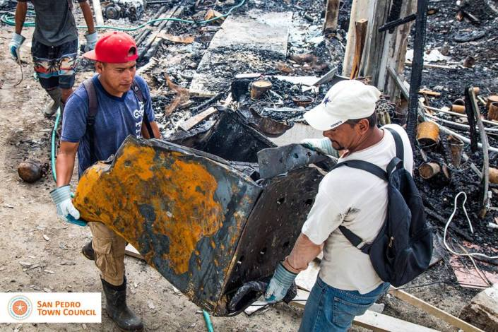 Burned out remains of a washing machine are removed from the rubble in downtown San Pedro, Ambergris Caye, Belize on Tuesday, June 28.