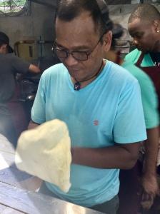 Hasni opens up the dough.